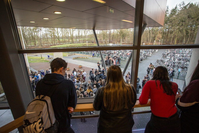 Medescholieren kijken naar de demonstratie vanuit de school