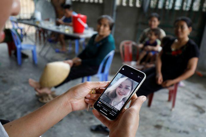 Een van de nabestaanden kijkt naar een foto van een slachtoffer.