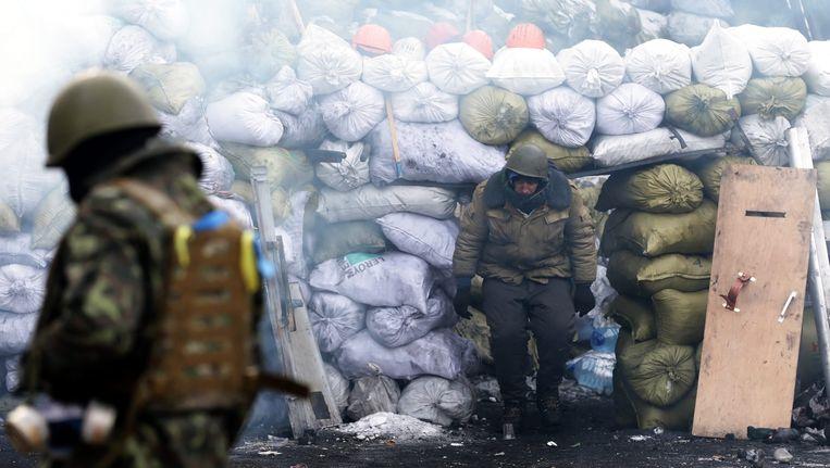 Februari 2014, demonstranten achter de barricades in Kiev. Begin vorig jaar liepen protesten tegen toenmalig president Janoekovitsj uit in bloedige rellen in de straten van Kiev. Beeld epa