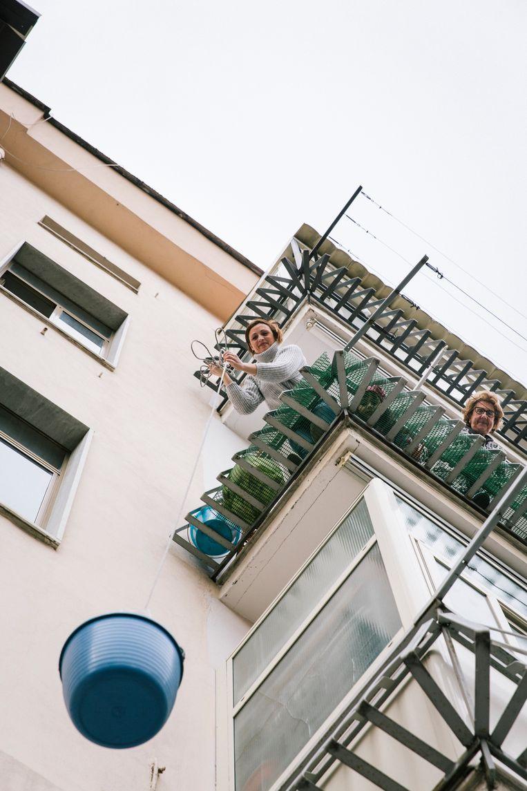 Een emmer wordt gebruikt om boodschappen het balkon op te hijsen. Beeld Gianni Cipriano