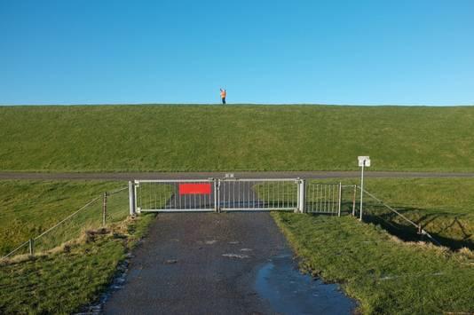 Landmeter op de dijk in noord-Friesland waar dit jaar het kunstwerk de 'Hollandweg' moet worden gerealiseerd.