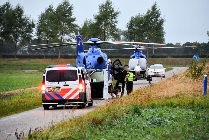 Twee politiehelikopters en twee politieauto's in Westdorpe.