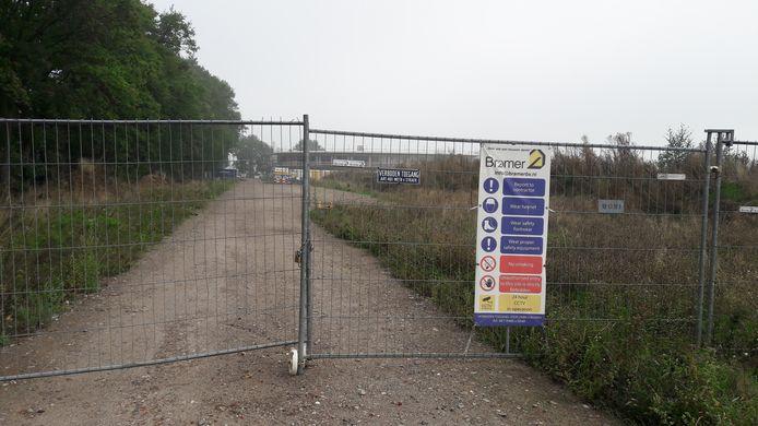 Het hek voor de bouwplaats zit al lange tijd op slot.
