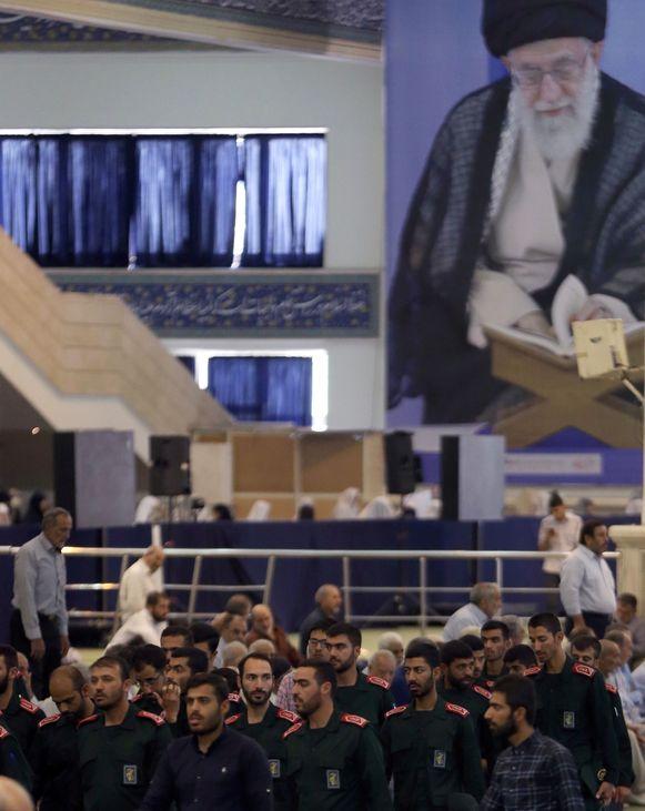 Met op de achtergrond een grote beeltenis van de Iraanse Opperste Leider, ayatollah Ali Khamenei, nemen leden van de Republikeinse Garde deel aan het vrijdaggebed in een moskee in Teheran. De Garde, Khamenei's eigen leger, speelt een cruciale rol in de 'tankeroorlog'.