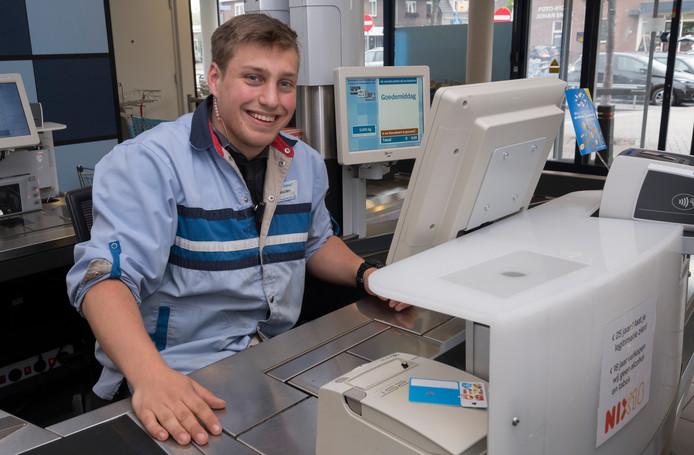 Willem Holthuysen (18) uit Milsbeek achter de kassa van Albert Heijn in Gennep. Zes uur per dag, schat hij dat hij per dag zit.