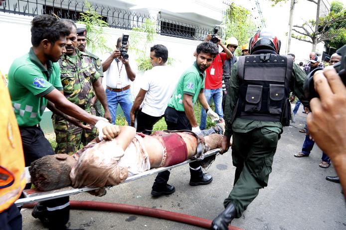 Een slachtoffer wordt geëvacueerd door autoriteiten in de Dematagoda buurt in Colombo.