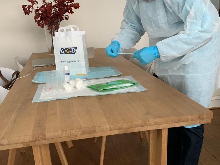 Een GGD-medewerker bereidt de corona-test voor in het huis van Edwin Klaasen. Beeld Edwin Klaasen