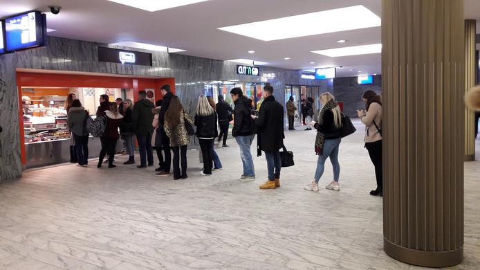 Als wordt omgeroepen dat er gratis koffie is, vormt zich al snel een rij reizigers voor de kiosk in de stationshal in Breda