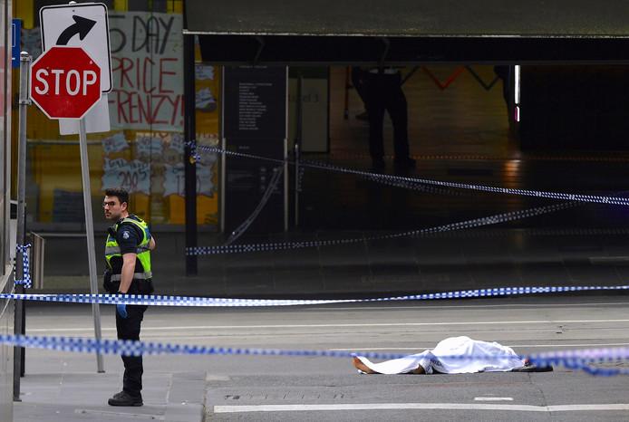 Een politieagent staat naast een bedekt lichaam in Bourke Street op de plaats van het incident.