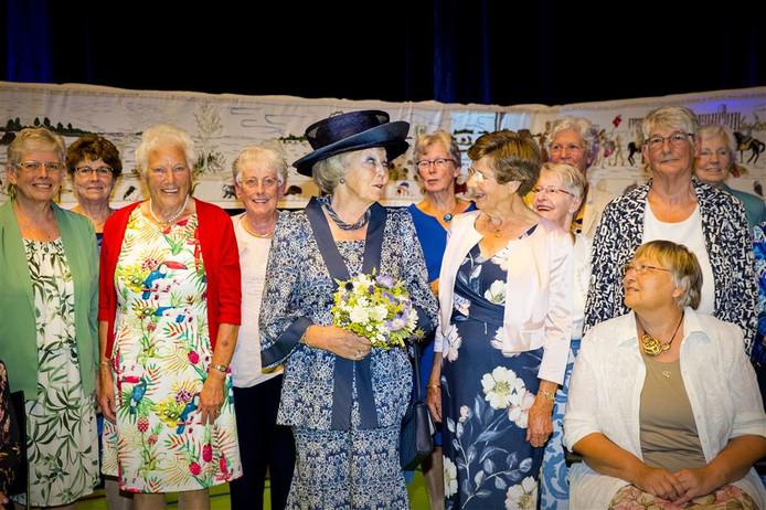 Prinses Beatrix  temidden van de vrijwilligsters die het wandkleed gemaakt hebben.