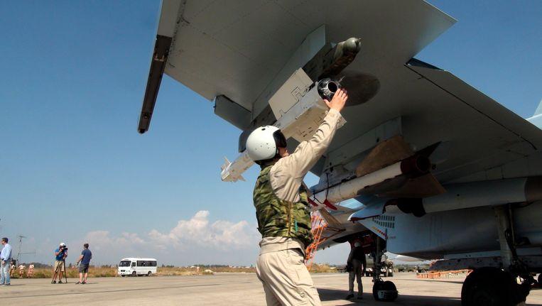 Een Russische piloot checkt de raketten onder een Su-30 op de Syrische luchtmachtbasis Hmeimim. Beeld ap