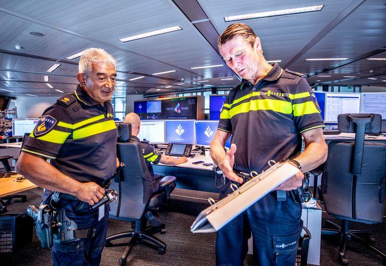Max Daniel (links) met een van zijn teamleden in de operation room op het hoofkantoor landelijke politie in Driebergen. Beeld Raymond Rutting / de Volkskrant