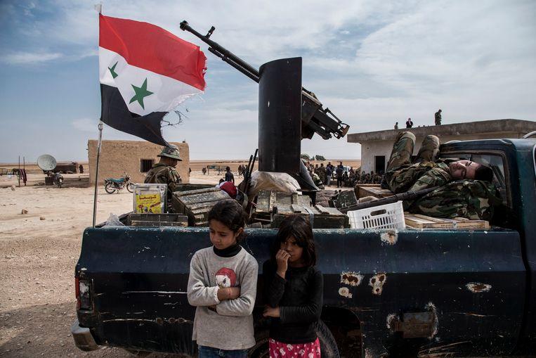 Kinderen bij een legervoertuig van de Syrische overheidstroepen in Tal Tamr.
