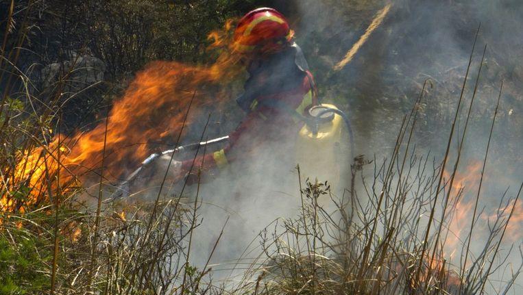 Een lid van een militaire eenheid blust een brand op Mallorca, in de buurt van Andratx. Beeld afp