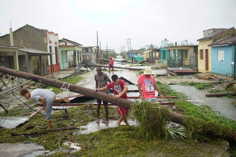 Cubanen lopen door een verwoeste straat in de kustplaats Caibarien. Beeld REUTERS