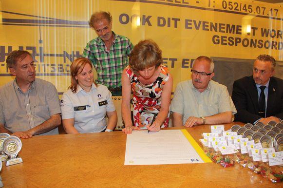Maria Hermans, mama van Falco, ondertekent het SAVE-charter. Ook de burgemeester, schepenen en de korpschef ondertekenden het document.