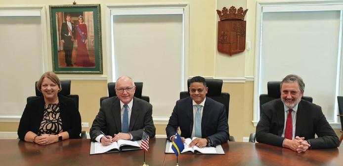Premier Eugene Rhuggenaath (2e van rechts) en de Amerika's ambassadeur in Nederland Pete Hoekstra (2e van links) tijdens de ondertekening van het Verdrag.