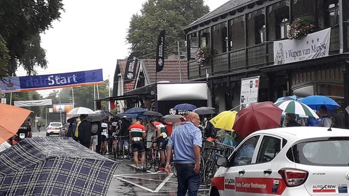 De wielrenners schuilen tijdens één van de vele regenbuien vanmiddag