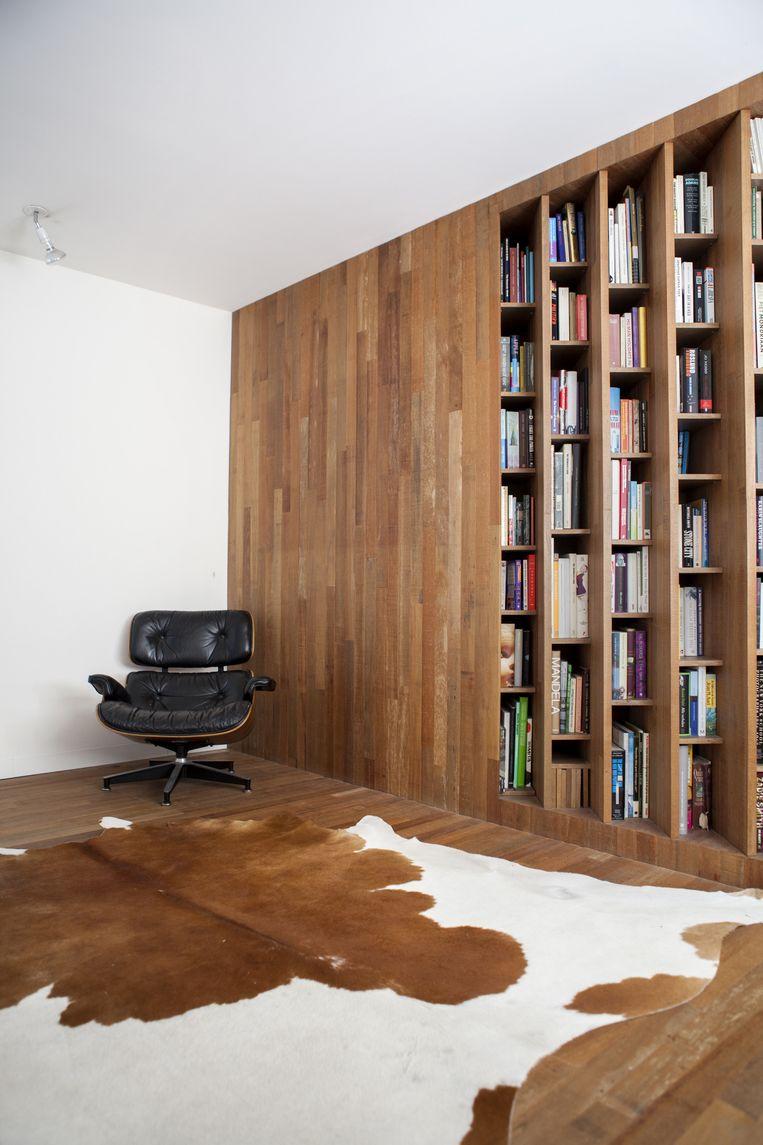 'De Eames-stoel komt van een van de eerste medewerkers van Herman Miller in Amerika, inmiddels een oud baasje; zijn kinderen vonden hem niet mooi en hij wilde dat-ie bij iemand terecht zou komen die hem wél waardeerde.' De boekenkast is een ontwerp van X+L architecten. Beeld Marie Wanders
