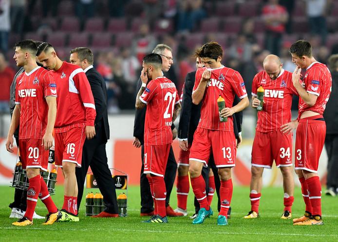 De spelers van FC Köln druipen af na de thuisnederlaag tegen Rode Ster.