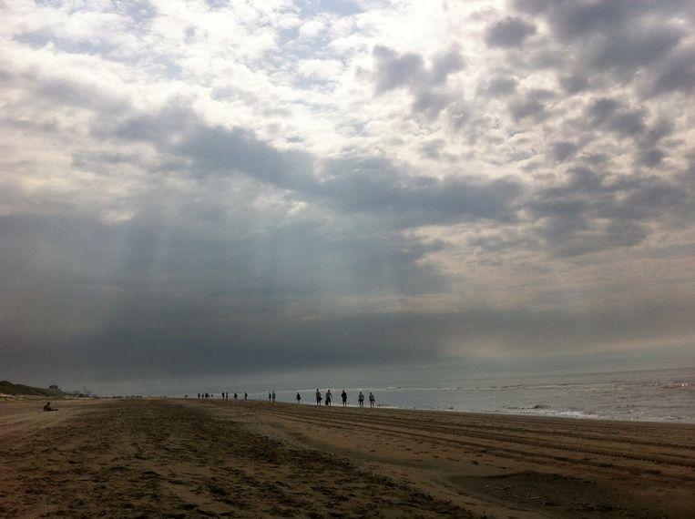 Wandelaars op zondag op het strand. Beeld null