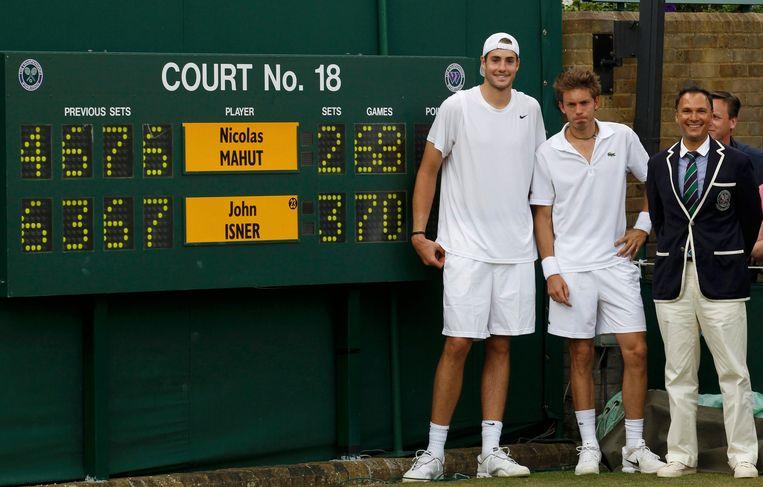 John Isner (links) en Nicolas Mahut staan bij het scorebord na hun marathonpartij in 2010 op Wimbledon.
