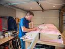 Van Beek aan het werk in zijn garage. ,,Het volledige vliegtuig kan ik bouwen op een werkbank van 1 bij 3 meter. Alleen de vleugels monteren gebeurt buiten.''