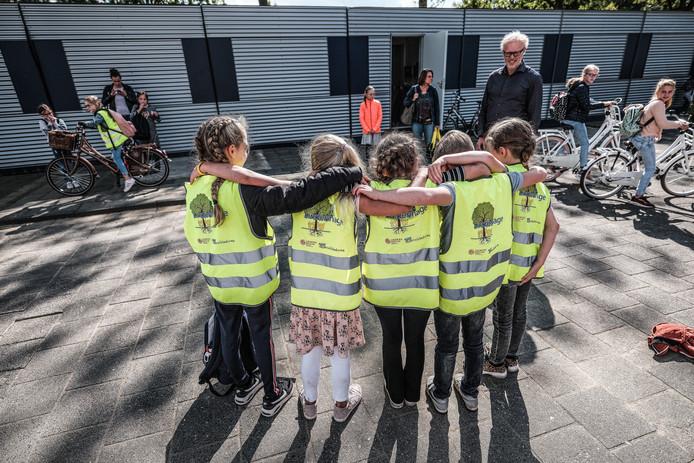 In felgekleurde gele hesjes fietsen leerlingen van de basisscholen Lindenhage en het Kofschip van en naar hun tijdelijke schoolgebouwen in de wijk Schrijvershoek. Foto : Jan Ruland van den Brink