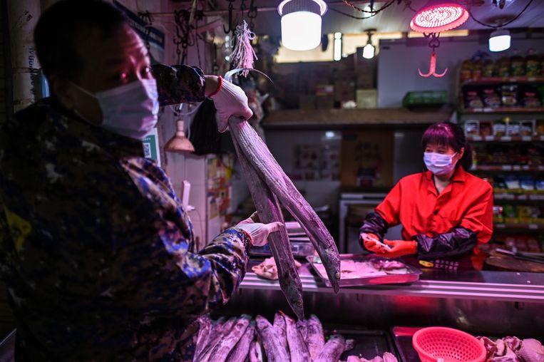 Op een markt in Wuhan wordt weer volop vis verkocht. Veel mensen dragen nog handschoenen en mondkapjes ter bescherming. Beeld AFP