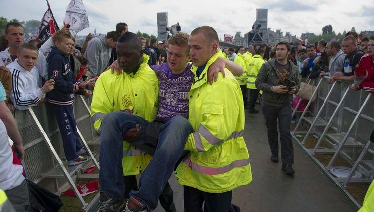 Een man wordt uit de feestende massa op het Museumplein gehaald door hulpverleners. Tijdens de huldiging van de Ajax-selectie voor het behalen van de dertigste landstitel zijn gewonden gevallen als gevolg van de drukte. Foto Beeld anp