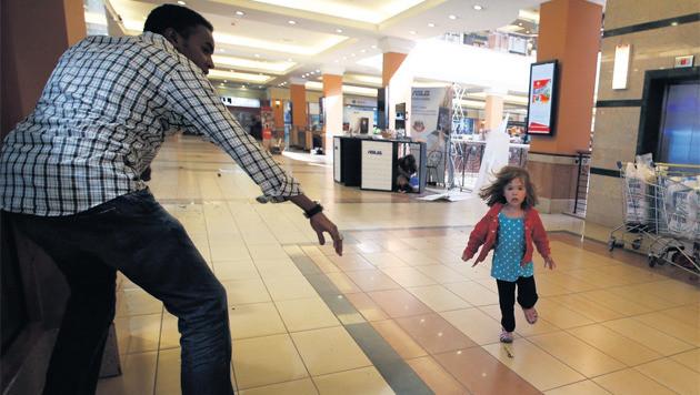 Het beeld dat de wereld over gaat: Abdul brengt de kleine Portia in veiligheid.