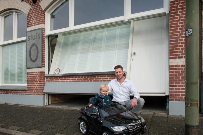 Jeroen Steringa en zijn zoontje voor de bijzondere garagedeur bij sluis 0 aan de Zuid-Willemsvaart