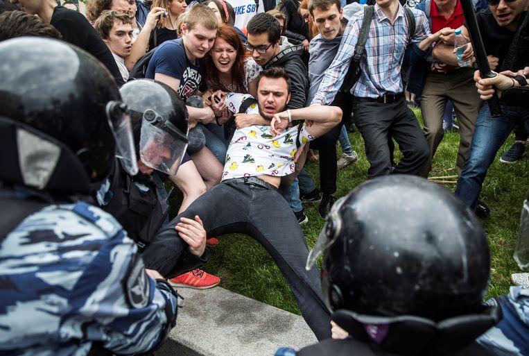 Aanhangers van de Russische oppositie proberen te voorkomen dat de politie Roeslan Sjaveddinov arresteert bij een demonstratie in Moskou, twee jaar geleden. Sjaveddinov, een naaste medewerker van oppositieleider Aleksej Navalny, werd deze week voor dienstplicht naar het afgelegen eiland Nova Zembla gestuurd. Beeld REUTERS