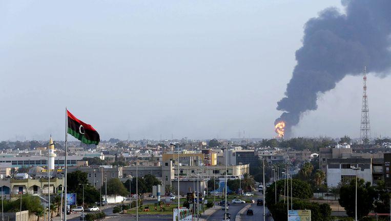 Zwarte rook stijgt op van een brandstofopslagplaats vlakbij het vliegveld van Tripoli. Beeld EPA
