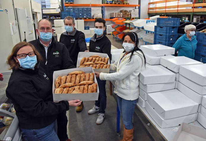 Leden van Cargill Cares overhandigen Miriam Hemelsoet (r) van Voedselbank Zeeuws-Vlaanderen dozen vol appelflappen.