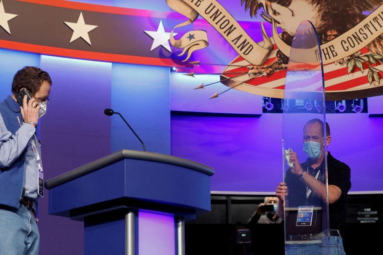 Bij de voorbereidingen van het laatste verkiezingsdebat vannacht tussen Trump en Biden wordt het plexiglas dat de opponenten van elkaar zal scheiden gereinigd. Beeld REUTERS