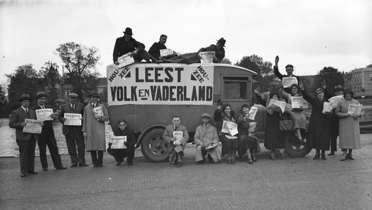 Een groep colporteurs toont een uitgave van het weekblad van de NSB, Volk en Vaderland. Beeld anp