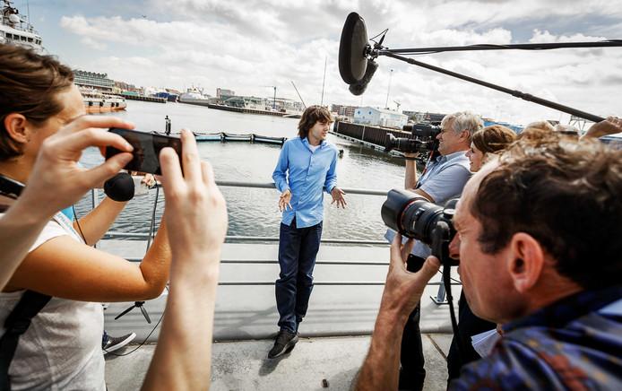 Boyan Slat staat de pers te woord met achter zich het Noordzee-prototype van The Ocean Cleanup.