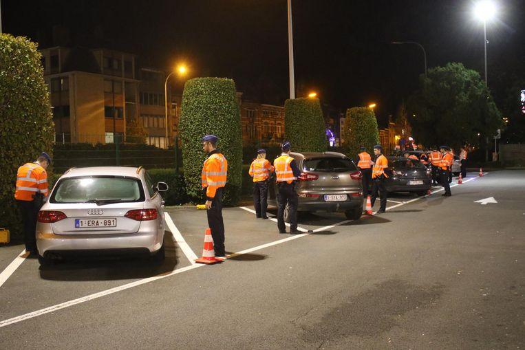 De agenten controleren de voertuigen zorgvuldig.