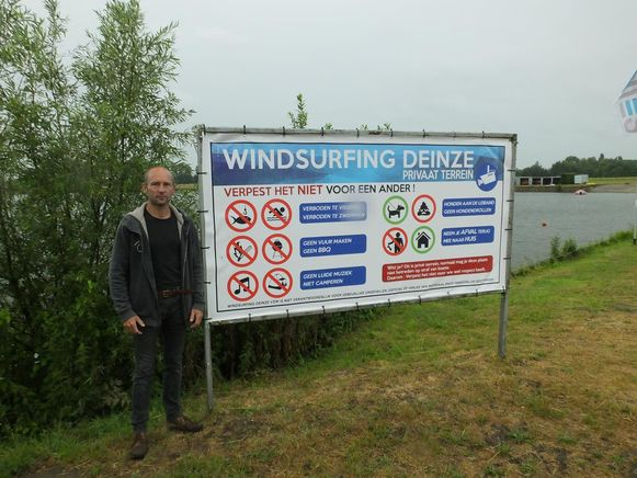 Voorzitter van Windsurfing Deinze Luc De Cooman bij het duidelijke waarschuwingsbord.