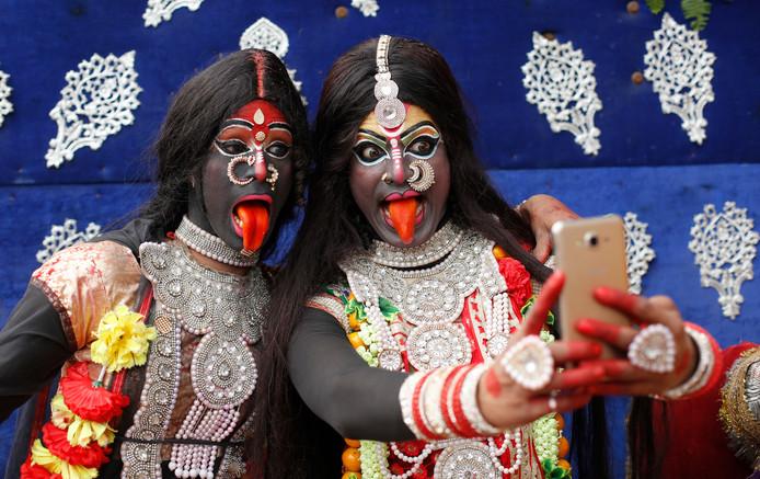 Twee Indiase meisjes nemen, verkleed als hindoegodin Kali, een selfie tijdens een processie bij het Mahashivratri-festival in Allahabad. Foto Rajesh Kumar Singh