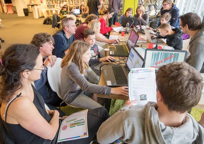 Muze Steiner Lovisa (links voor aan tafel) is aandachtig bezig met haar computer.  Coderdojo-vrijwilliger Marc Burgs (achter Muze) kijkt mee.