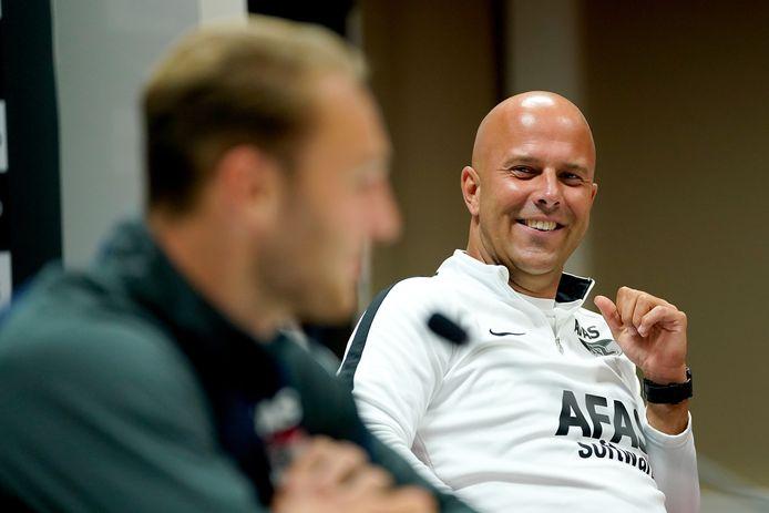 Trainer Arne Slot van AZ kijkt toe hoe Teun Koopmeiners antwoord geeft op de vragen.
