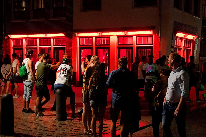 Toeristen vergapen zich aan prostituees op de Wallen.