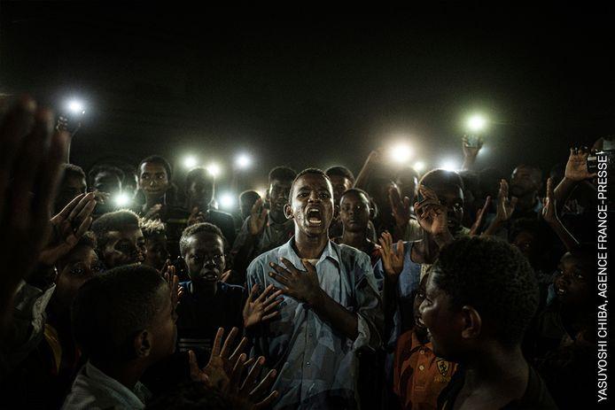 De Japanner Yasuyoshi Chiba won dit jaar de World Press Photo met een foto uit juni 2019 in Khartoem, Soedan. Demonstranten drommen samen rond een jongeman die een protestgedicht declameert.  Omdat de elektriciteit in de hoofdstad is uitgevallen, lichten ze hem bij met hun mobieltje.