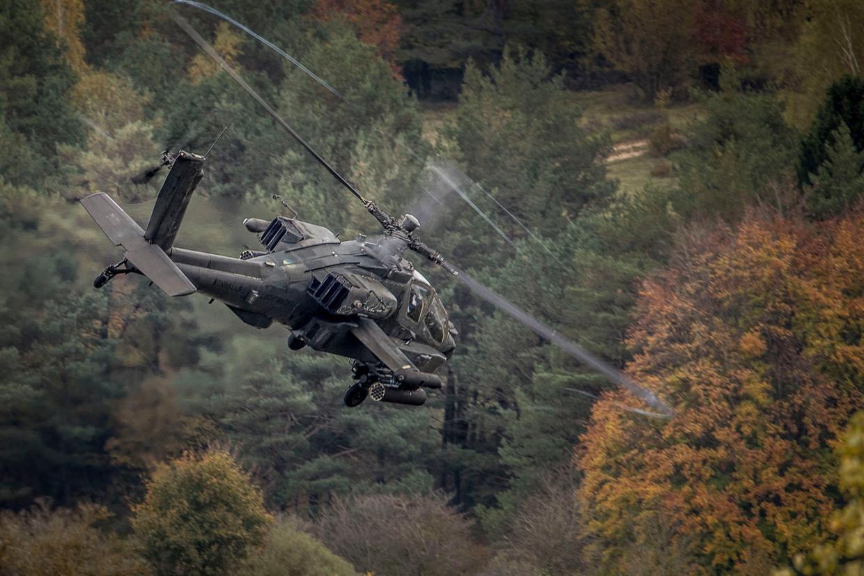 Een Apache scheert over de boomtoppen tijdens een Navo-oefening.