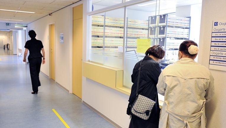 Patiënten melden zich bij een balie in een ziekenhuis. © anp Beeld