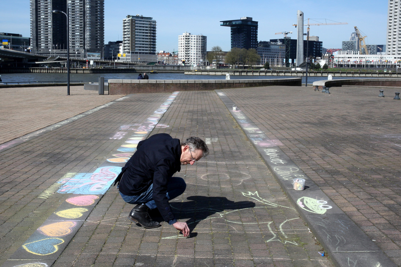 Rotterdammer Arie Westeneng maakt met krijt mooie creaties op straten en stoepen om iedereen een hart onder de riem te steken. Hij wordt er zelf ook erg vrolijk van.