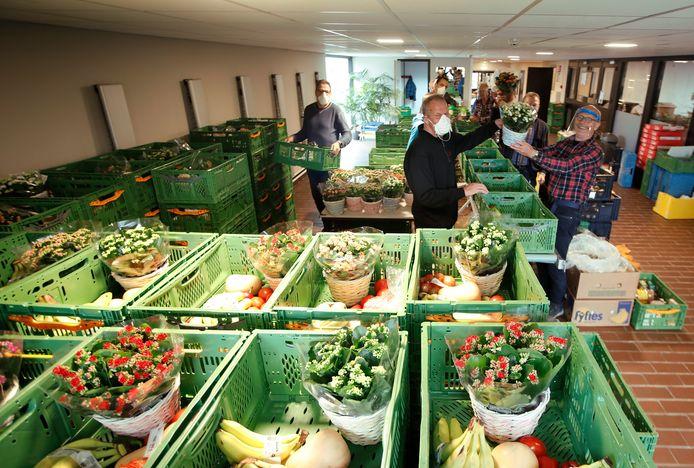 Vrijwilligers van de Westlandse voedselbank doen in de Ontmoetingskerk in Naaldwijk een kalanchoë bij de voedselpakketten.