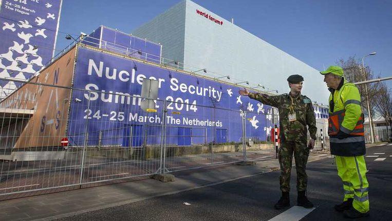 Een militair en een verkeersregelaar bij het gebouw van het World Forum, Beeld anp